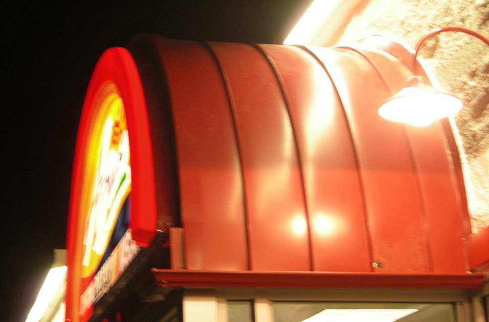 Red Radius Metal Roof Over A Store Entrance In Brooksville Florida